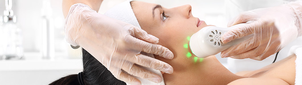 Women getting laser skin treatment on face.